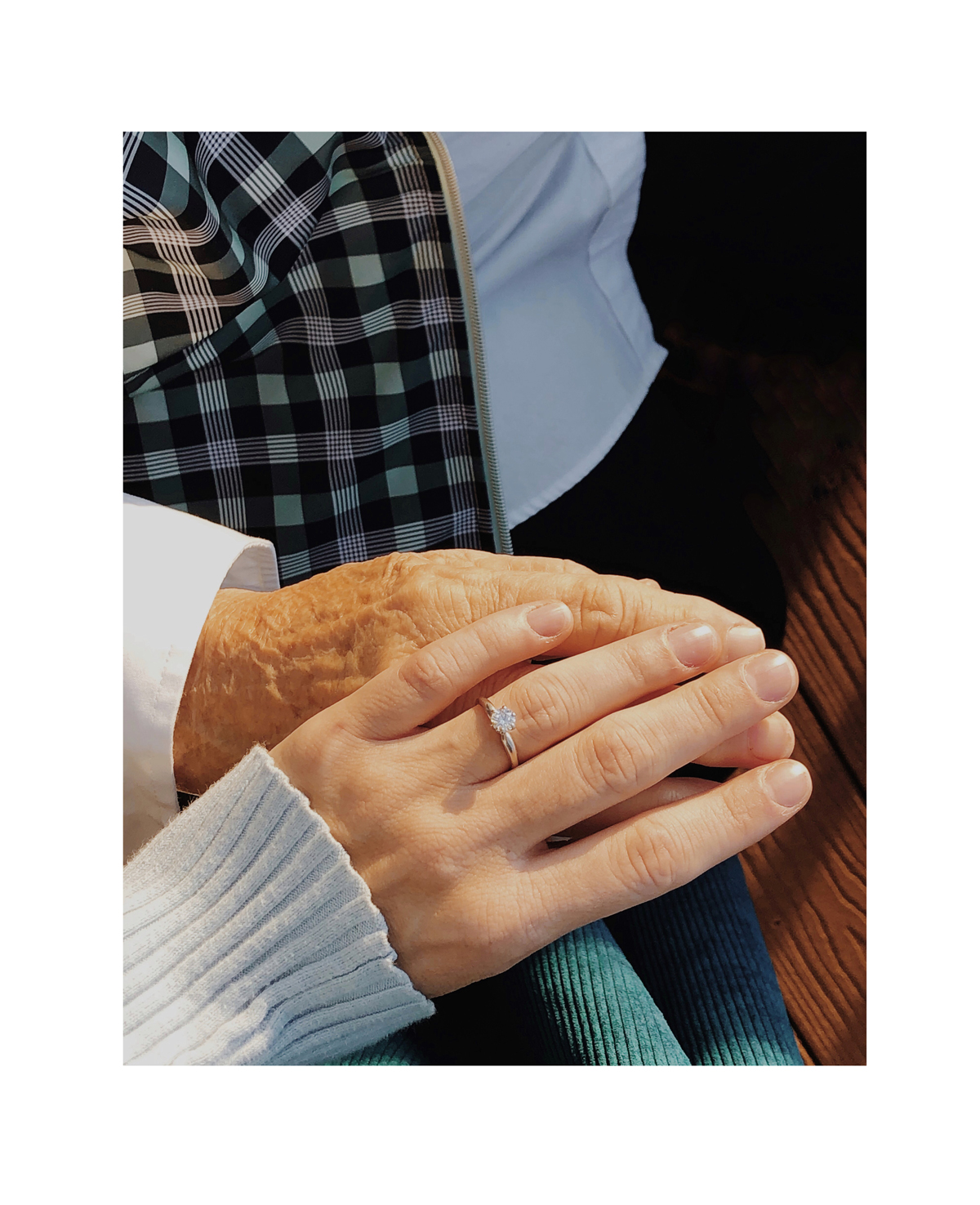Photo by Molly Lopez of hand with ring resting on hand of parent
