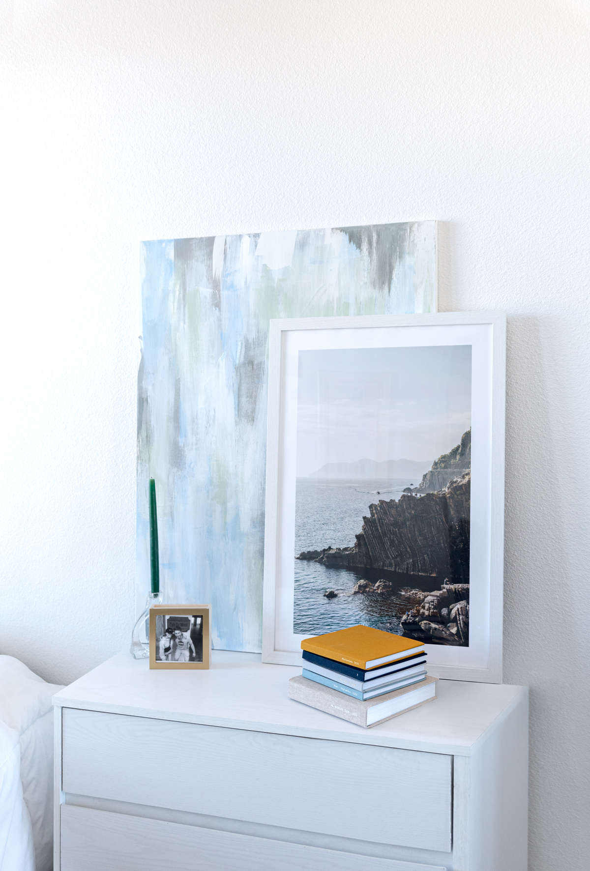 Artifact Uprising gallery frame, everyday photo books, and brass & wood display box on dresser