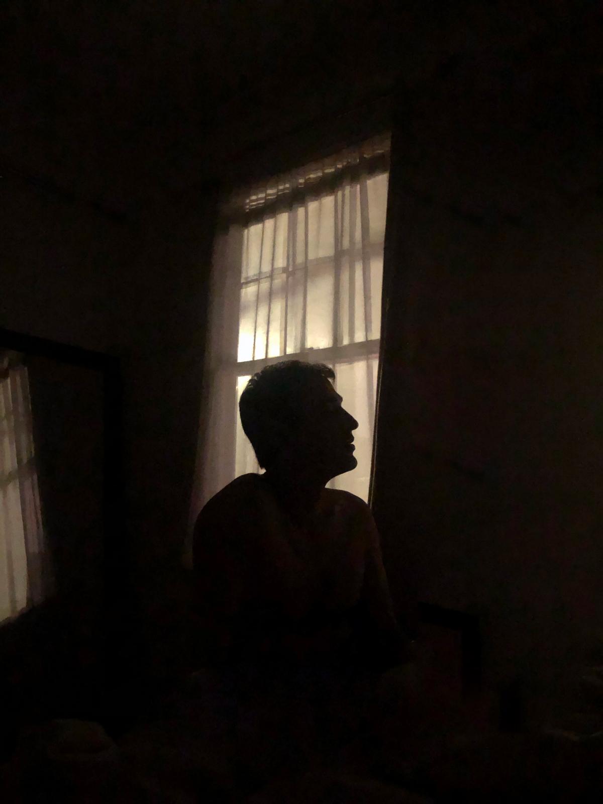 Portrait of man's dimly lit silhouette in front of window