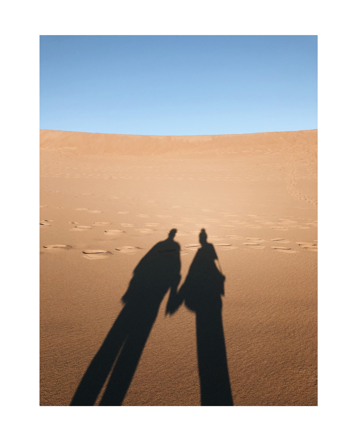 Photo of couple casting shadow onto desert sands by Molly Olwig