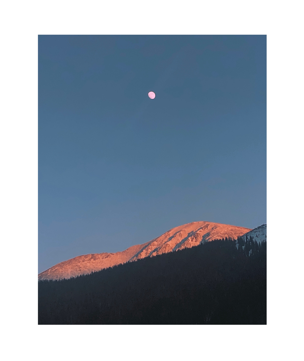 Photo of moon above snow-capped mountains by Molly Olwig
