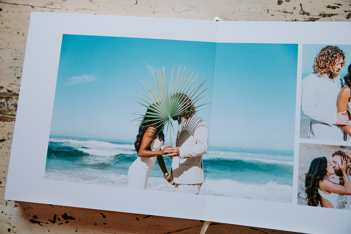 Signature Layflat Album opened to posed photos of bride and groom on the beach