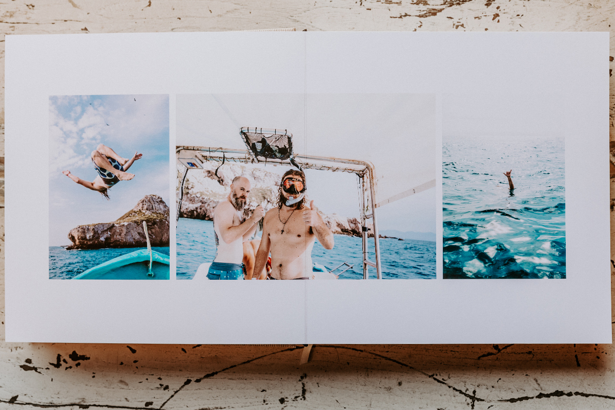 Signature Layflat Album opened to photos of groom and groomsmen on boat