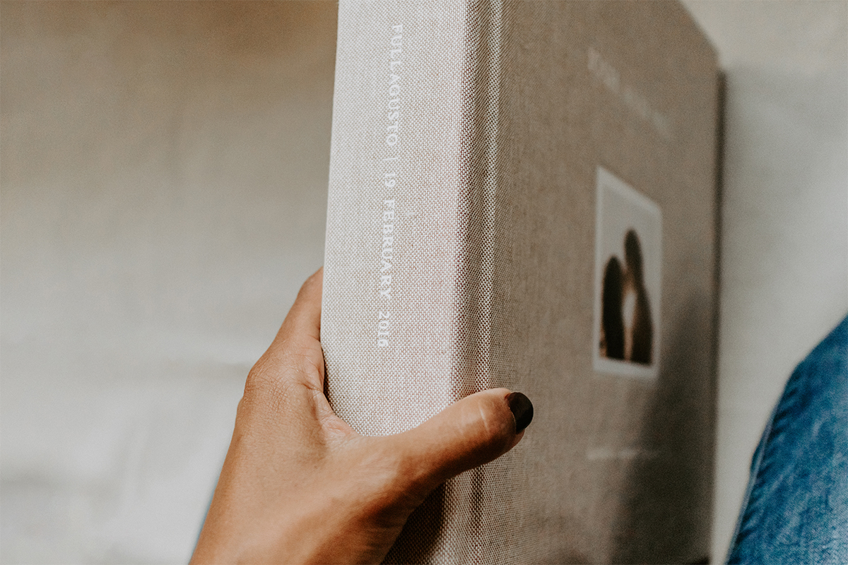 Woman's hands holding photo book by the spine