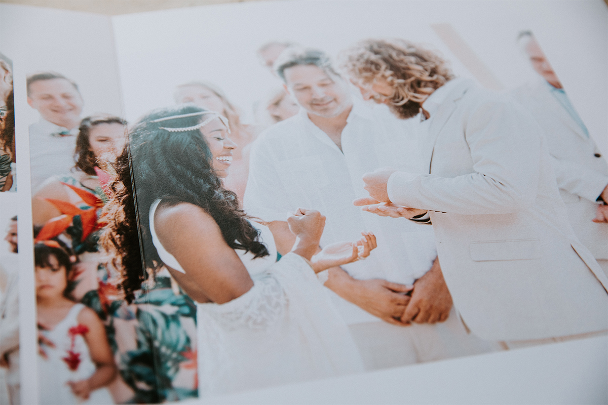 Zoomed in on album opened to image of bride and groom during ceremony