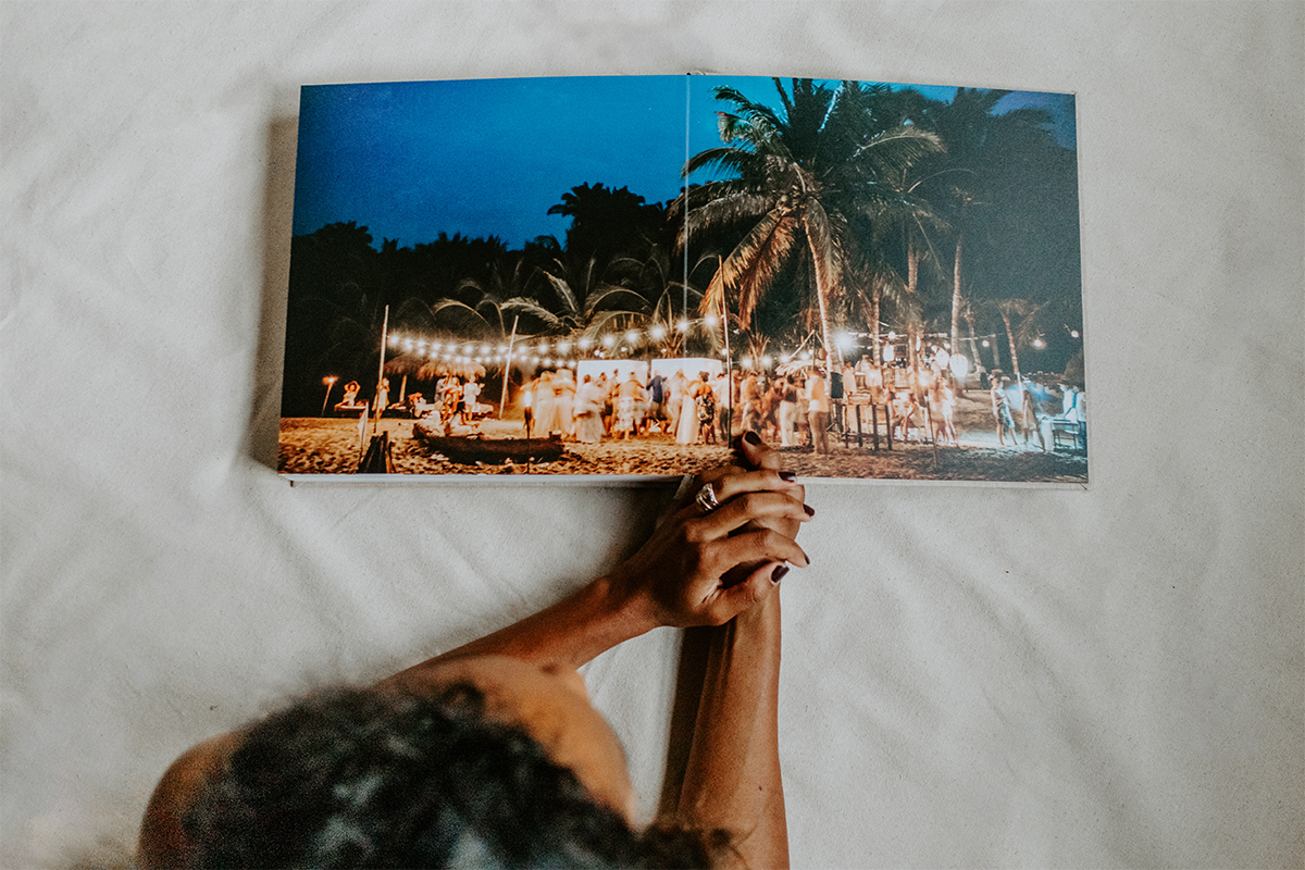 Signature Layflat Album opened to two-page panoramic image of reception on the beach at night