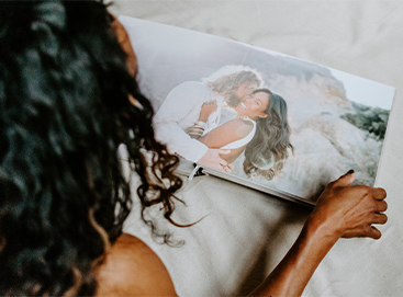 Woman flipping through Signature Layflat Wedding Album opened to two page panoramic image of bride and groom