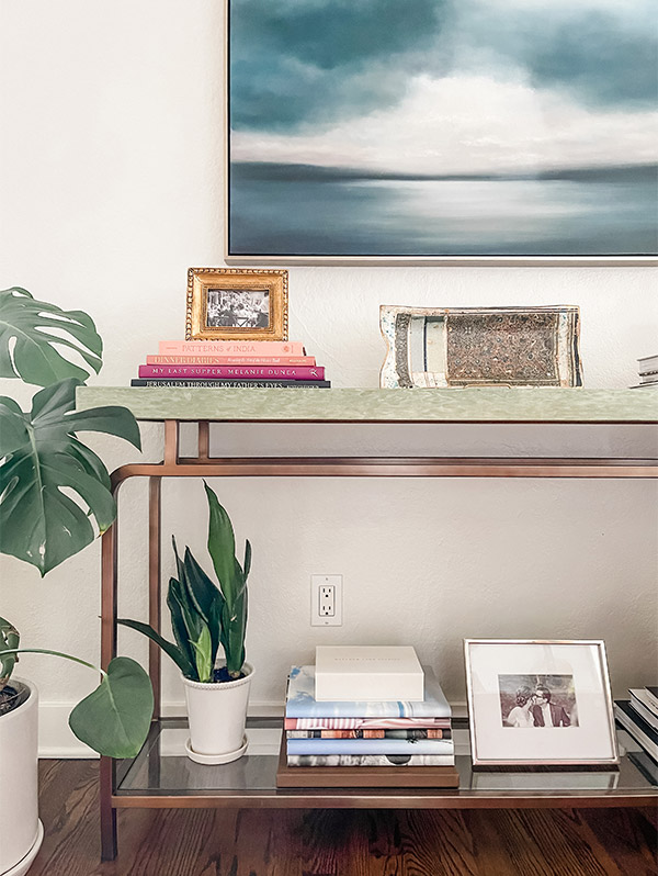 Console Table filled with decor including stack of Artifact Uprising Hardcover Photo Books