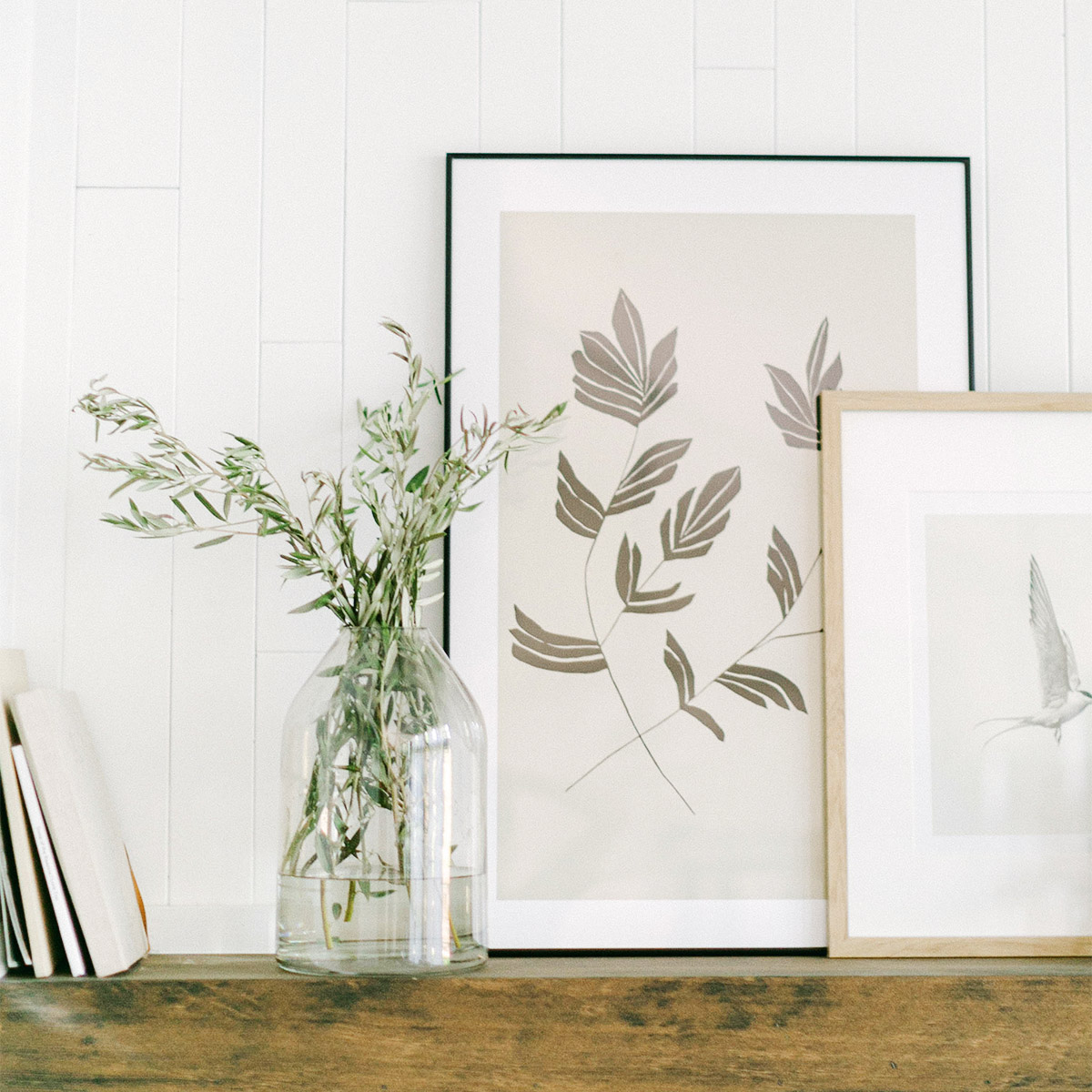Two frames layered on mantle next to vase of foliage