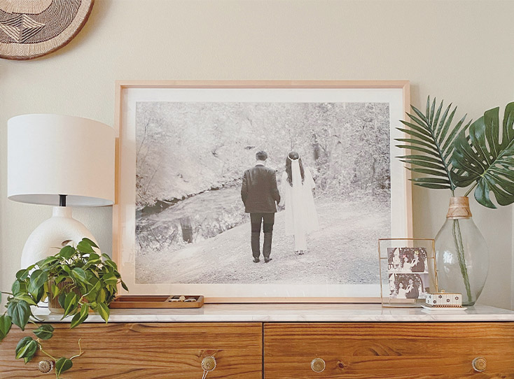 Large Artifact Uprising Gallery Frame with wedding photo atop mantle filled with plants and decor