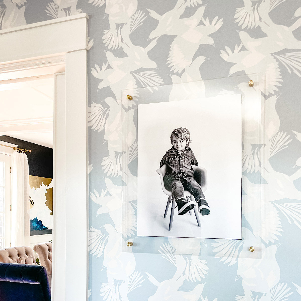 Artifact Uprising Floating Frame of child's portrait hanging on wallpapered wall