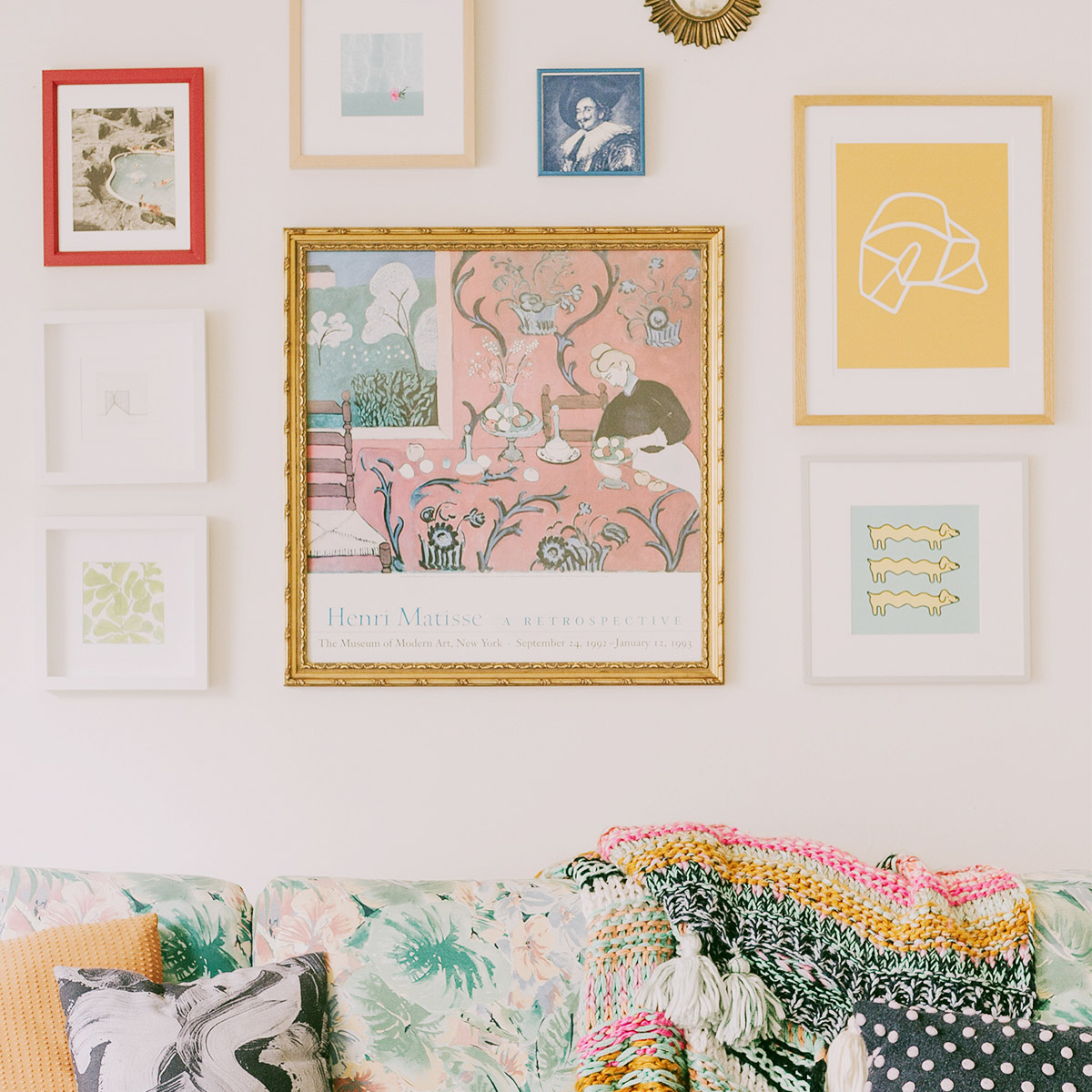 Vibrant gallery wall featuring Artifact Uprising frames hung above vintage pastel couch