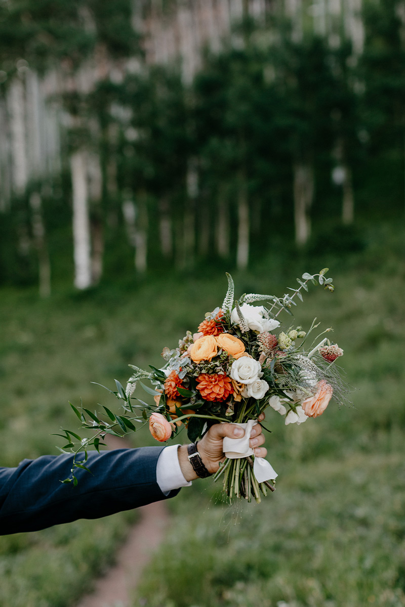 Hand holding up bridal bouquet