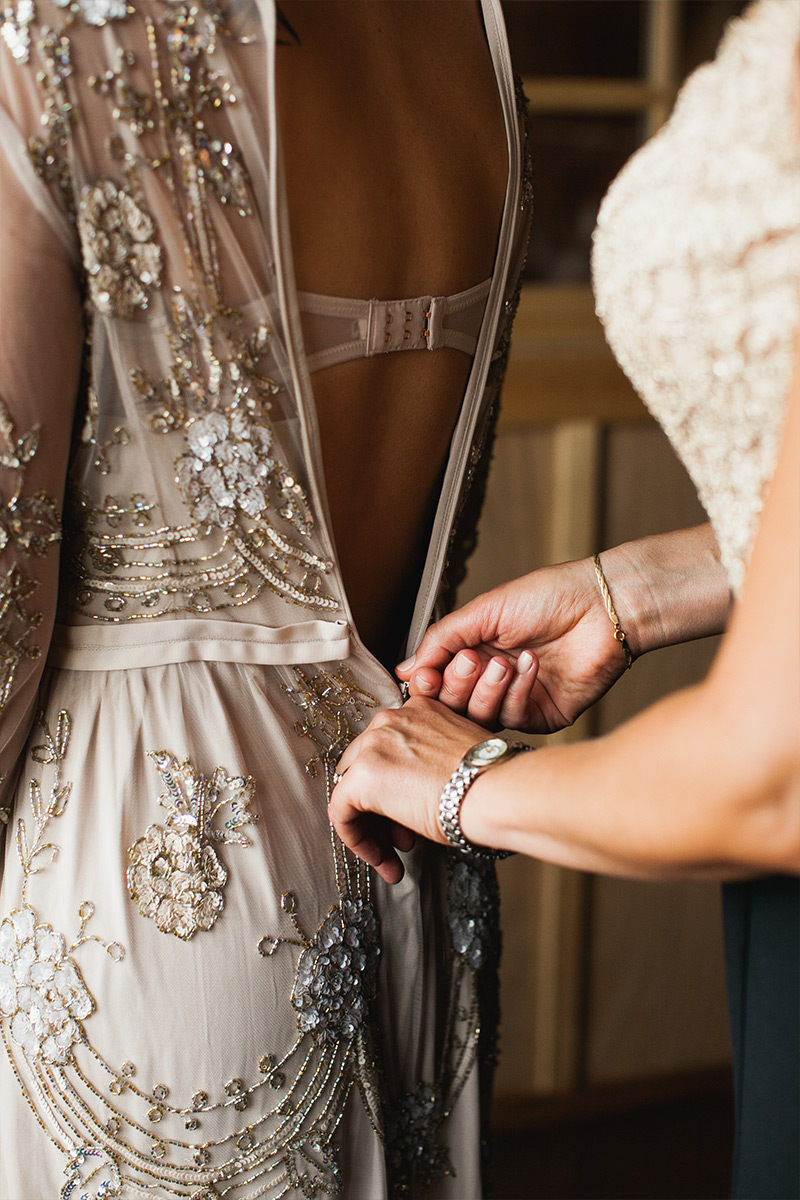 Mom zipping up bride's wedding gown