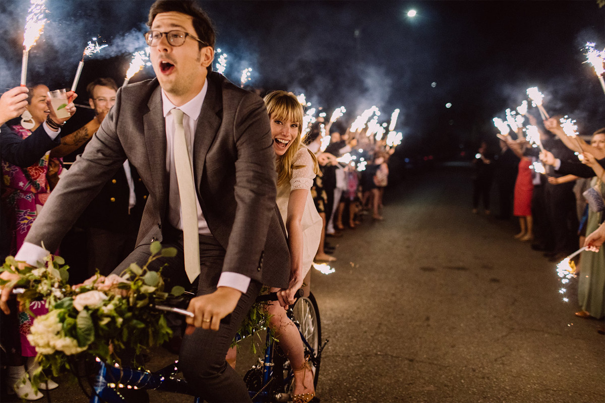 Bride and groom making final exit on a bicycle