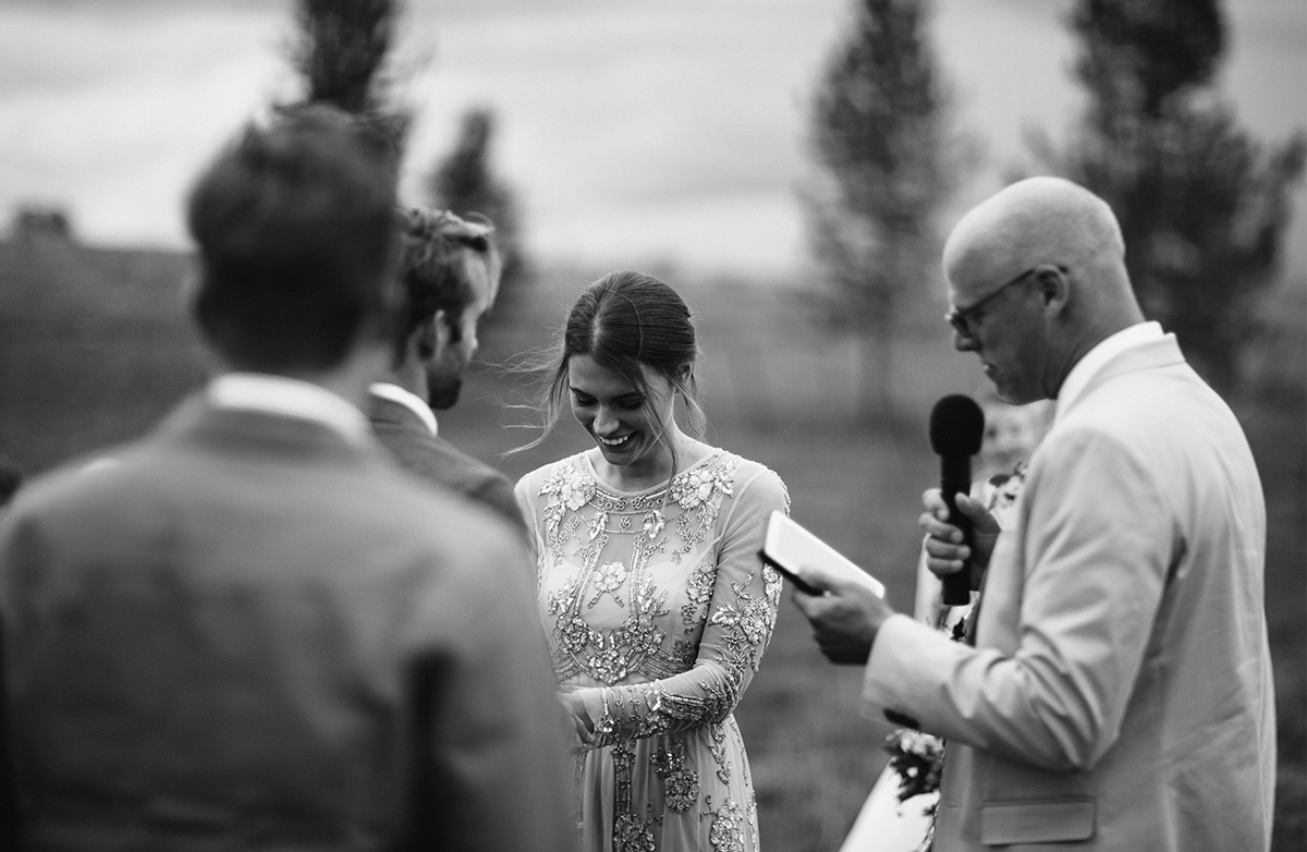 Bride laughing as wedding officiant says something funny