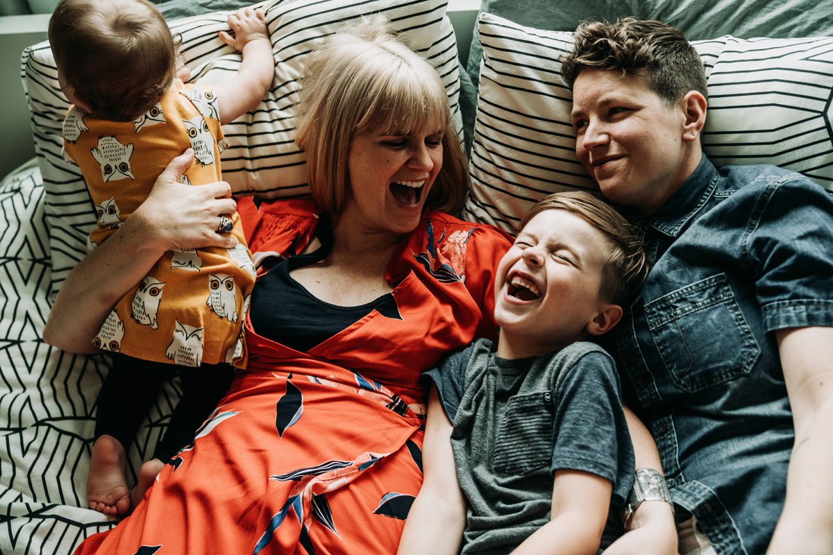 Family with two young children laughing as they lay in bed