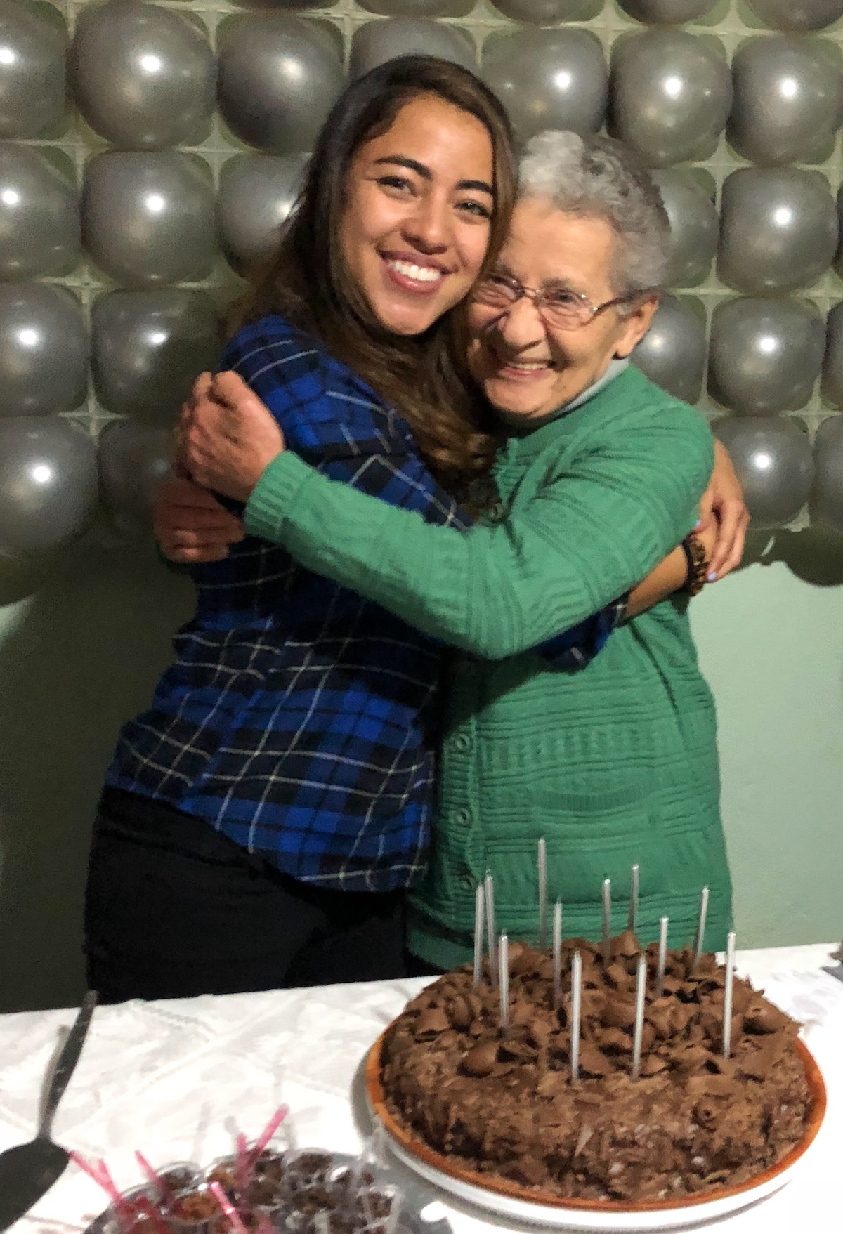 Photo of grandma and granddaughter embracing by birthday cake
