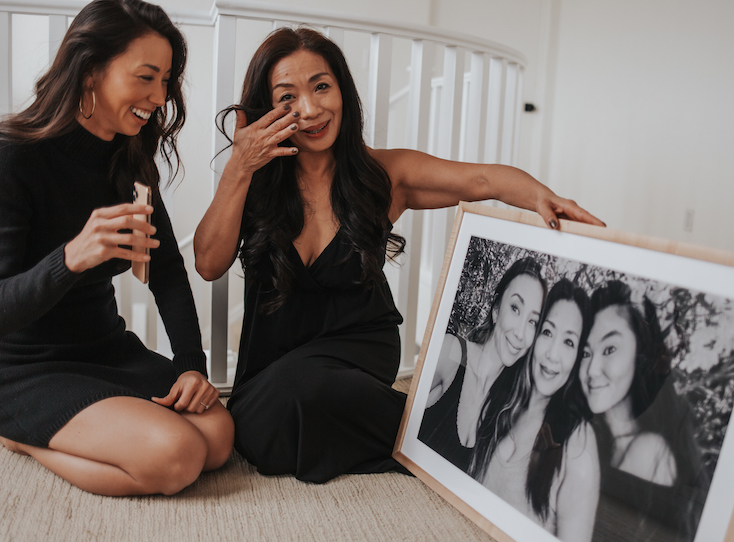Mom wiping tear from eye as she receives framed photo from daughter
