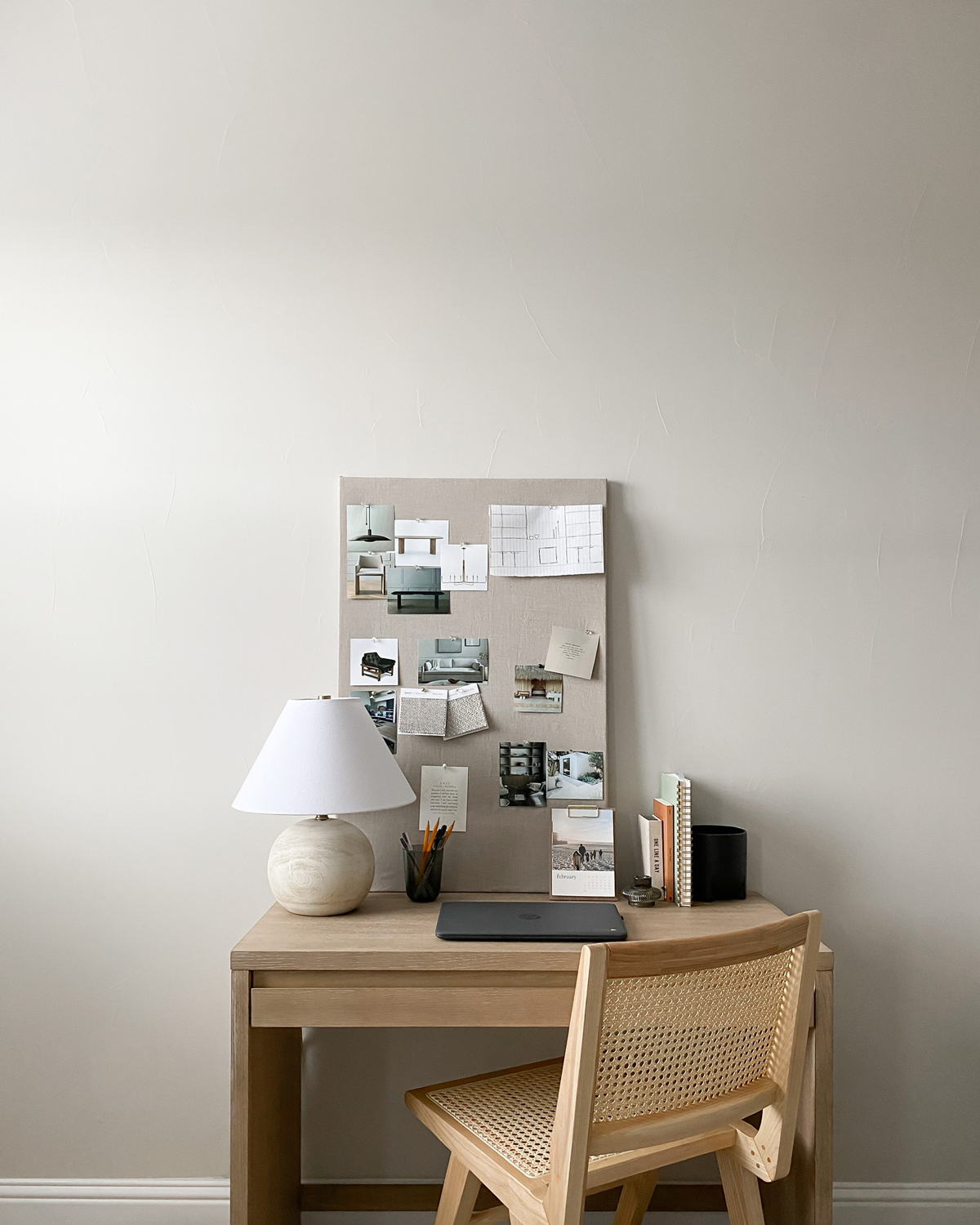 Bulletin board adorned with pictures standing on small desk with wooden chair