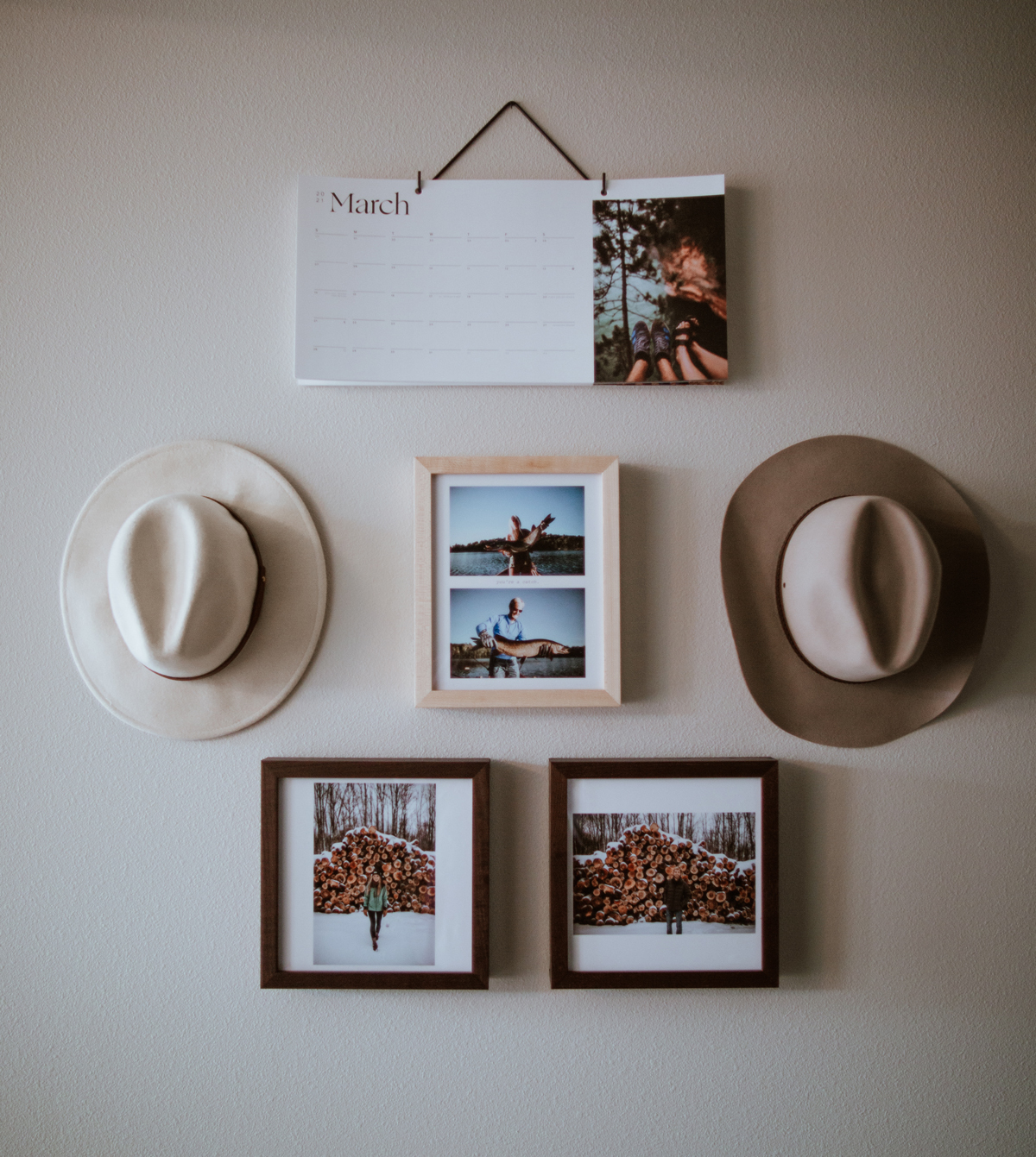 Combination of hats hung on wall next to Artifact Uprising Wall Calendar and Frames