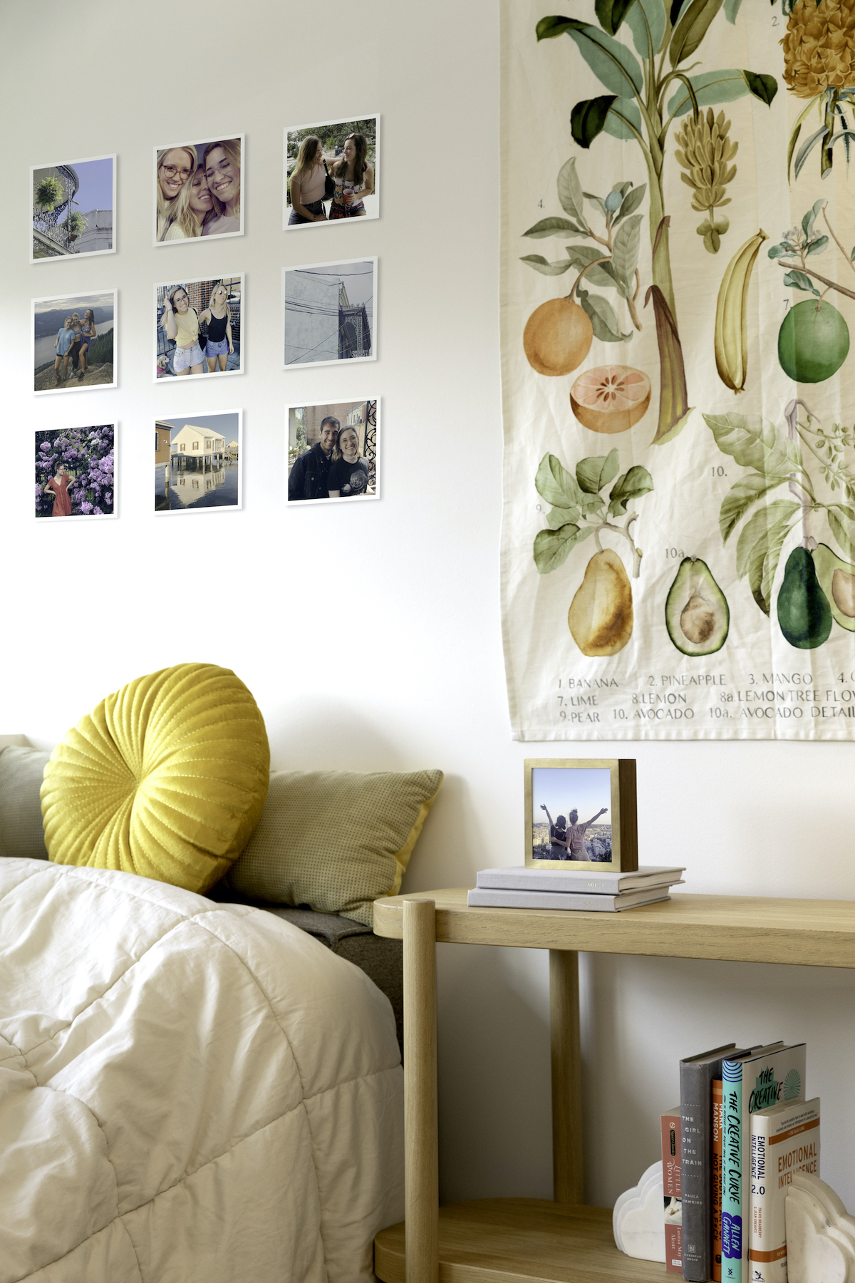 Artifact Uprising prints above bed next to tapestry and nightstand with photo display box