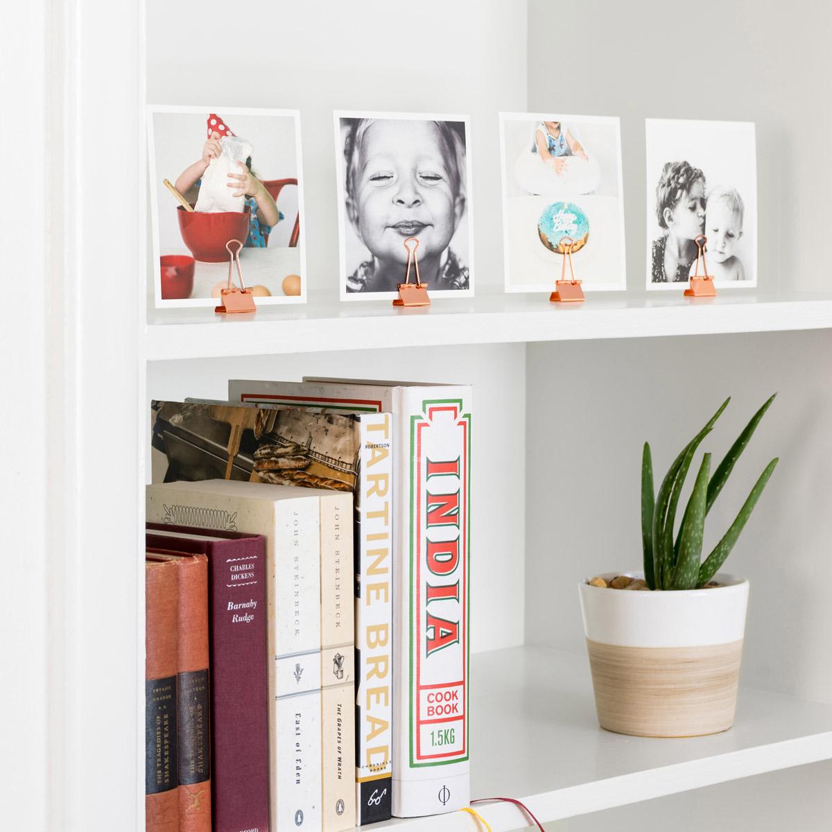 Binder clips used as photo holders to display Artifact Uprising Photo Prints on bookshelf