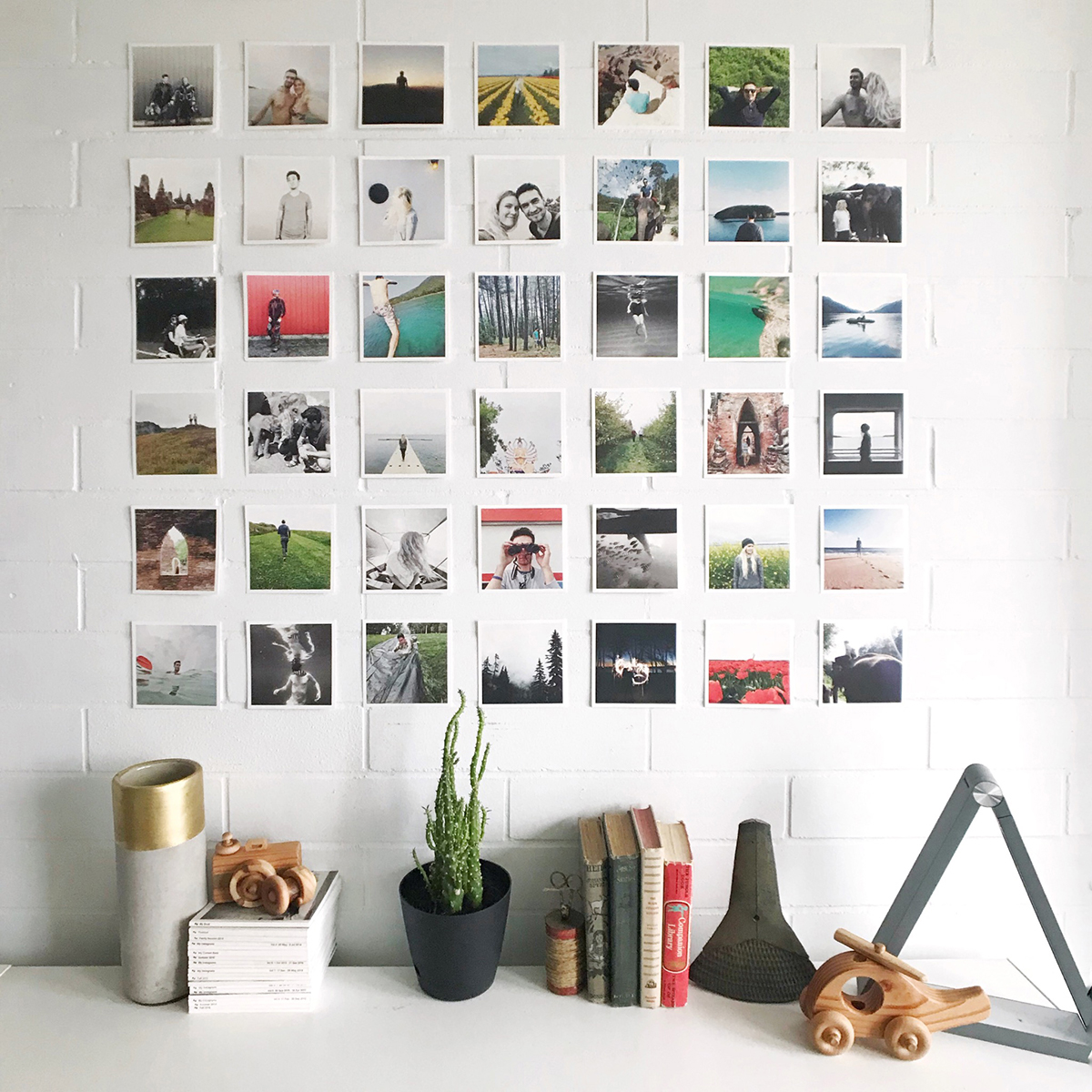 Artifact Uprising photo prints taped into a grid pattern on wall