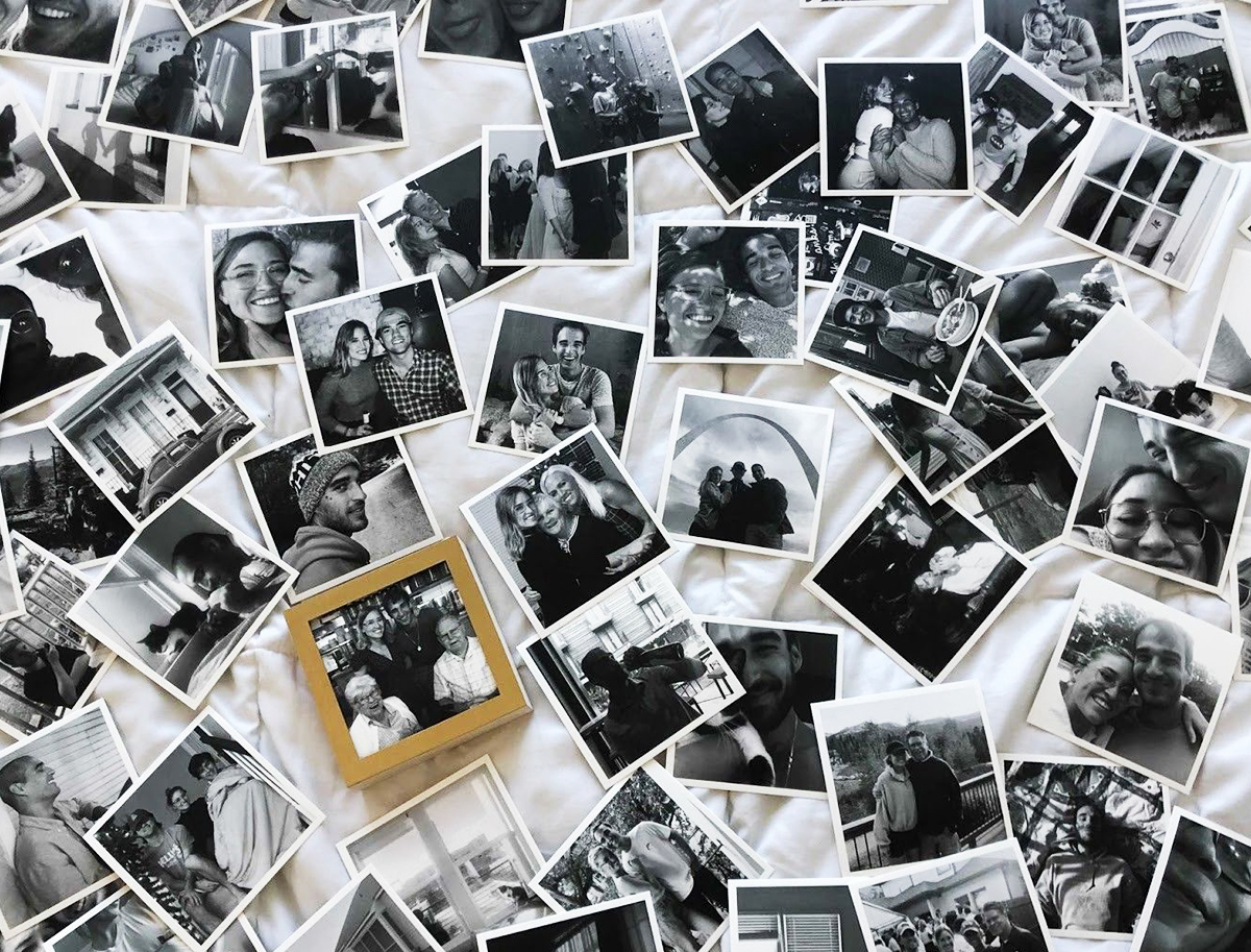 Hundreds of black-and-white Artifact Uprising photo prints scattered on bed