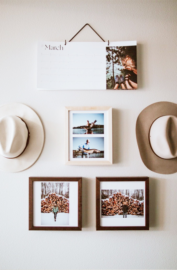 Mix-and-match gallery wall featuring two hats, three framed photos, and an Artifact Uprising Modern Wall Calendar