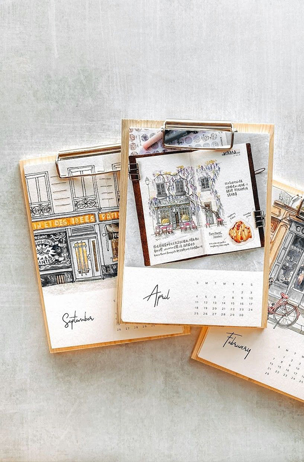 Artifact Uprising Wood Calendar featuring beautiful drawings of travel scenes for every month
