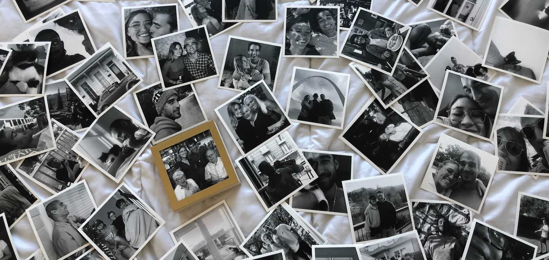 Artifact Uprising photo prints scattered all over bed featuring black-and-white photos