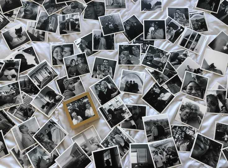 Black and white Artifact Uprising photo prints scattered all over bed