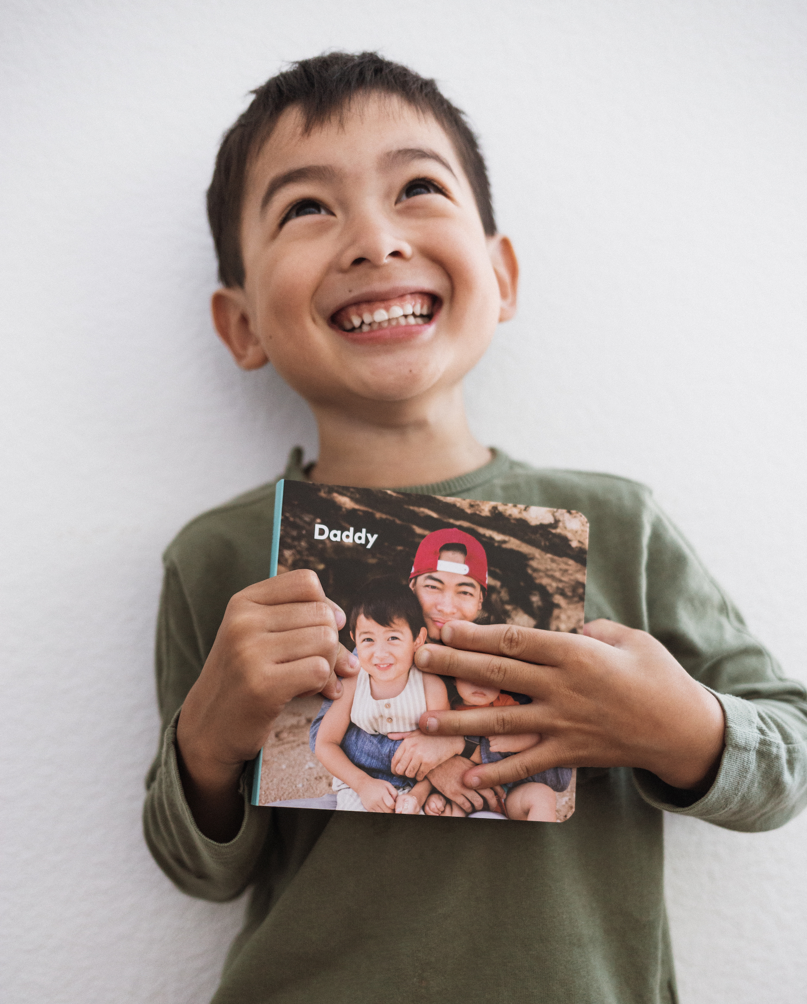 Little boy holding up Artifact Uprising Board Book titled Daddy