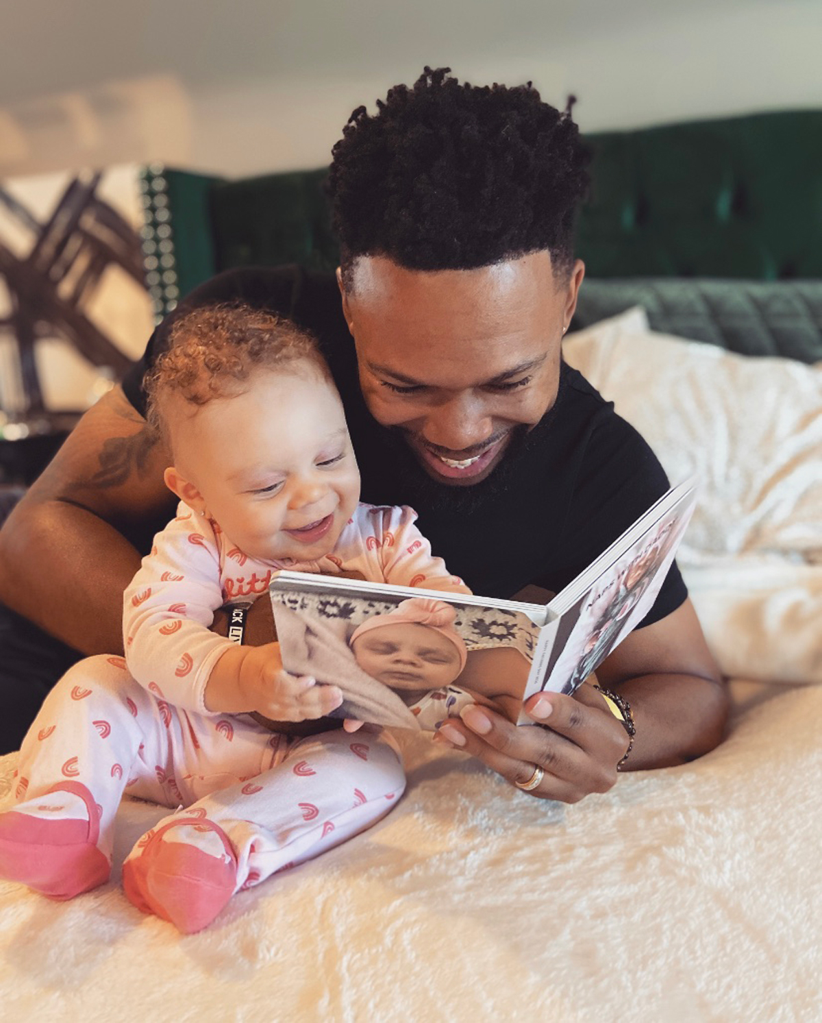 Father and baby daughter reading Artifact Uprising Board Book together on bed