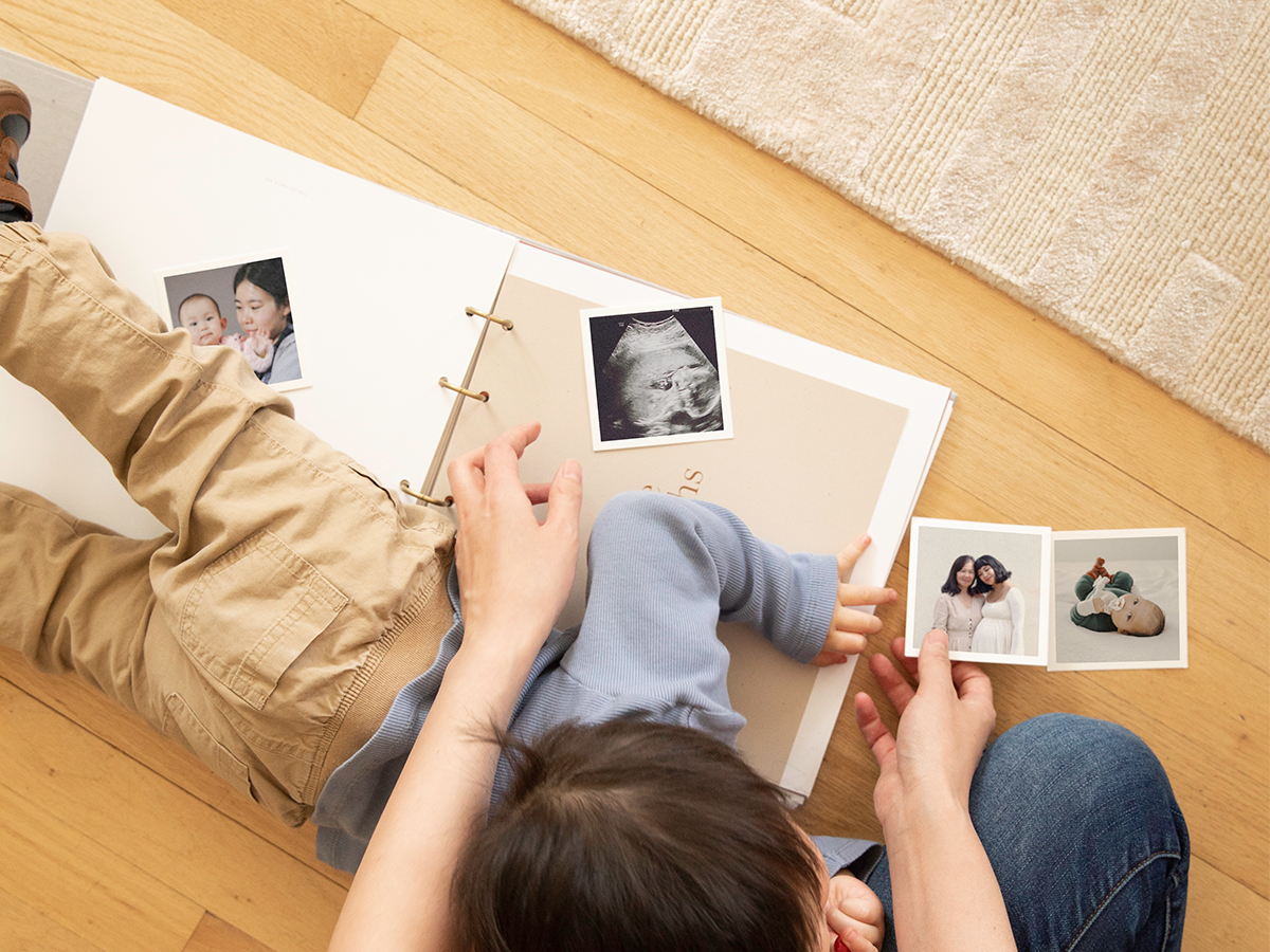 Little lying across Artifact Uprising Story of You Photo Book as mom tries to fill it out