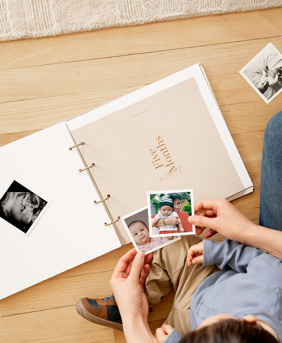 Artifact Uprising Story of You Photo Book opened to month five as mother and little boy choose prints to put inside