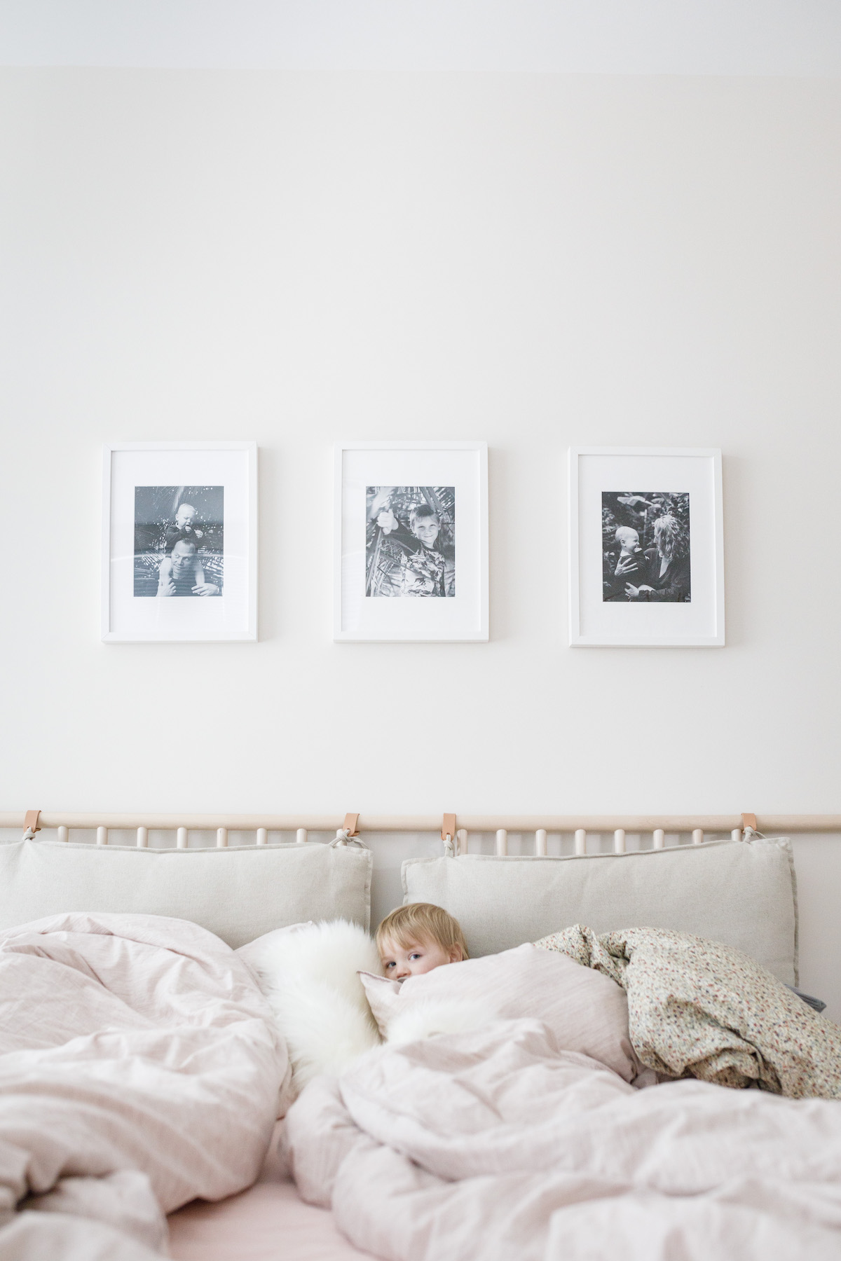 Child curled up under blankets with three Artifact Uprising Gallery Frames filled with family photos overhead.