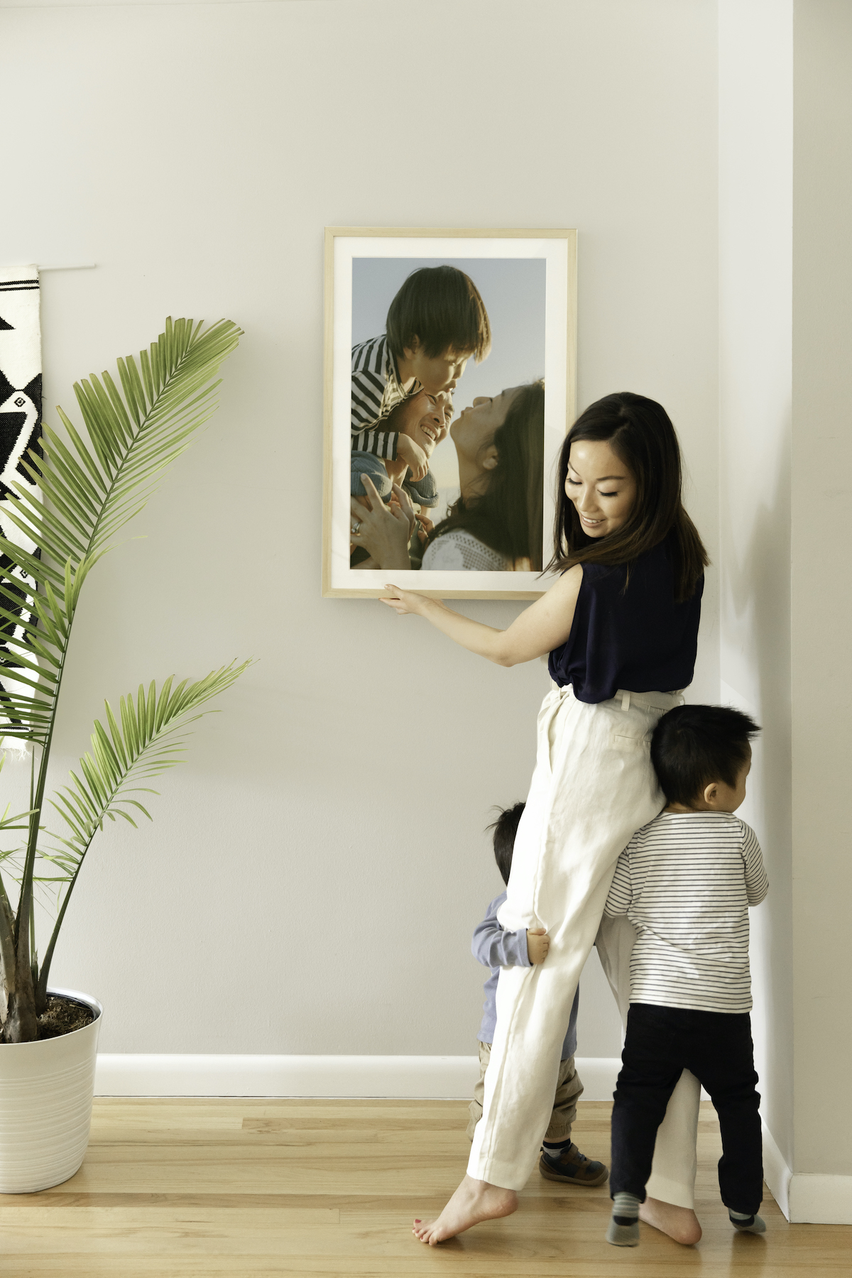 Mom hanging up Artifact Uprising Gallery Frame with two toddlers each hugging one of her legs