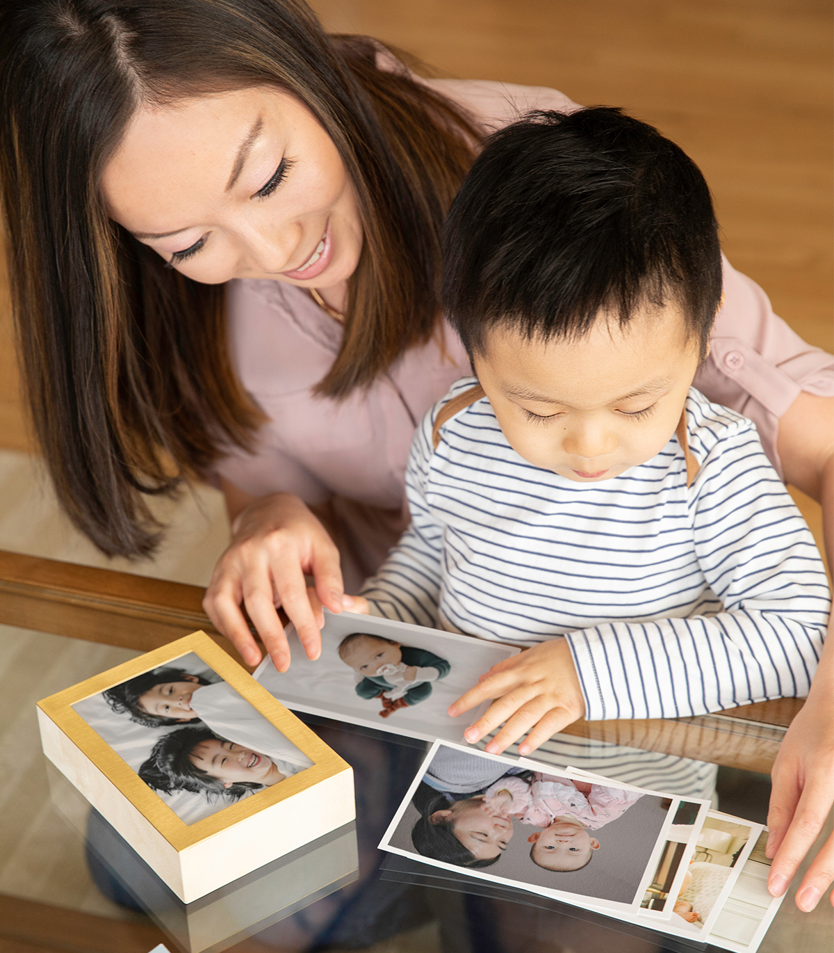 Mom and little boy choosing family photos to place inside Artifact Uprising Brass & Wood Display Box