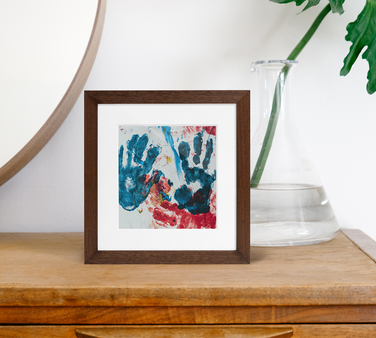Artifact Uprising Wooden Tabletop frame in walnut finish featuring children's handprints in paint on dresser next to mirror and plant