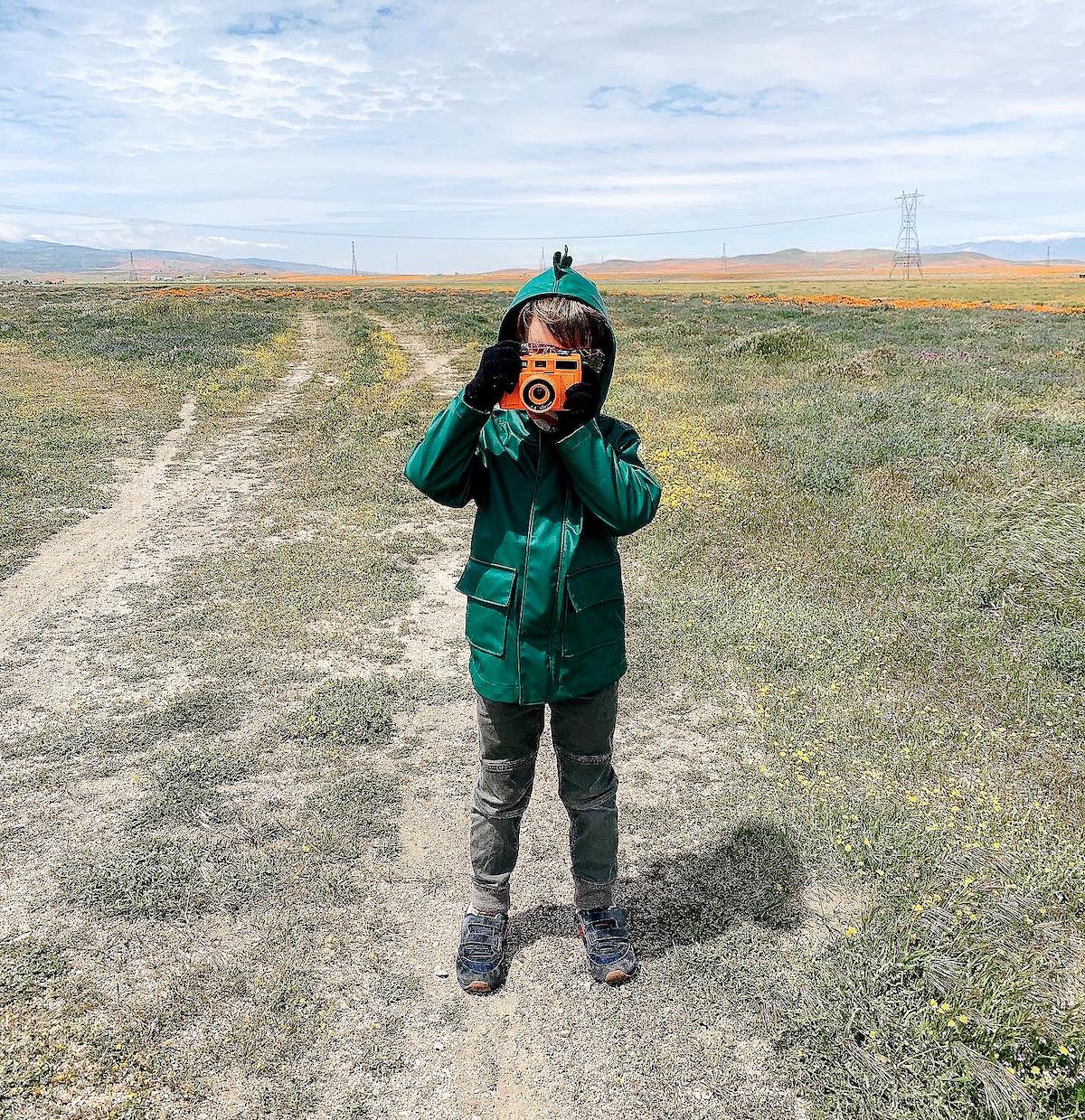 Little boy in field holding up camera