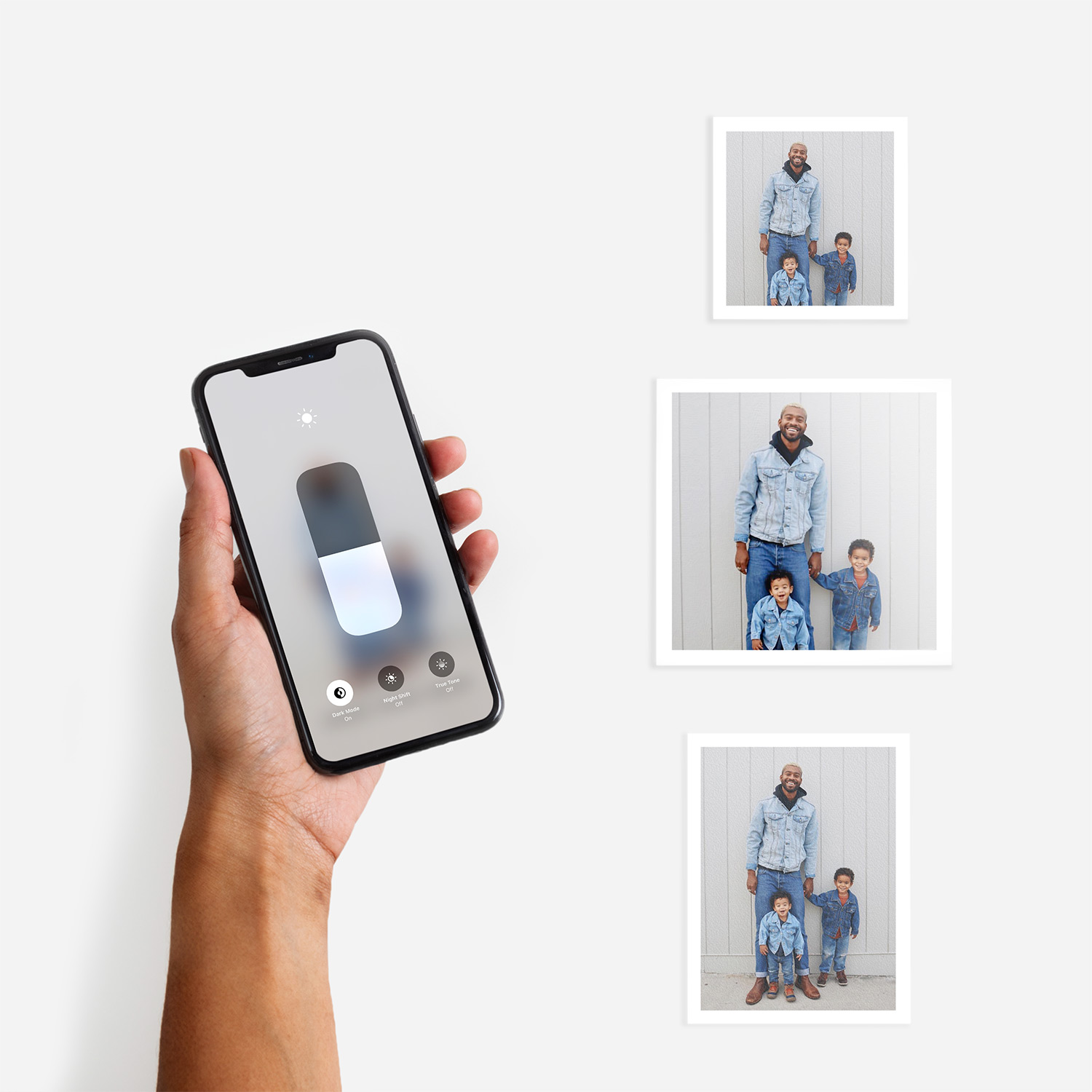 Hand adjusting screen brightness on an iphone next to three Artifact Uprising photo prints featuring family photos of a father and their children