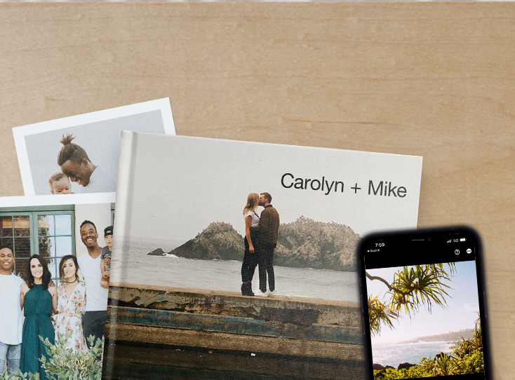 Artifact Uprising photo prints and photo book featuring family photos on table next to iphone