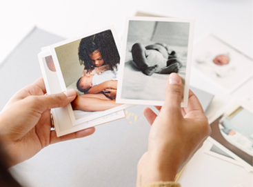 Woman's hands holding photos as she chooses which to put in her baby book