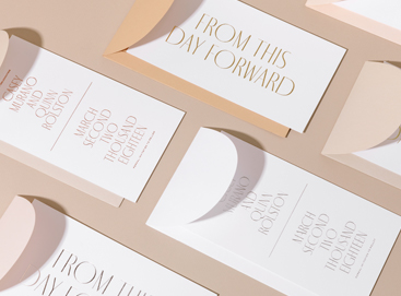 Different wedding invitation designs laid out on table
